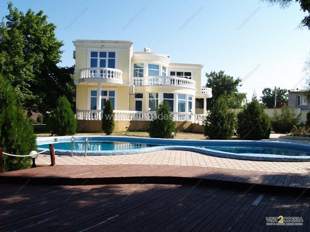 Decked BBQ area, trees, swimming pool at luxury villa in Odessa, Ukraine.